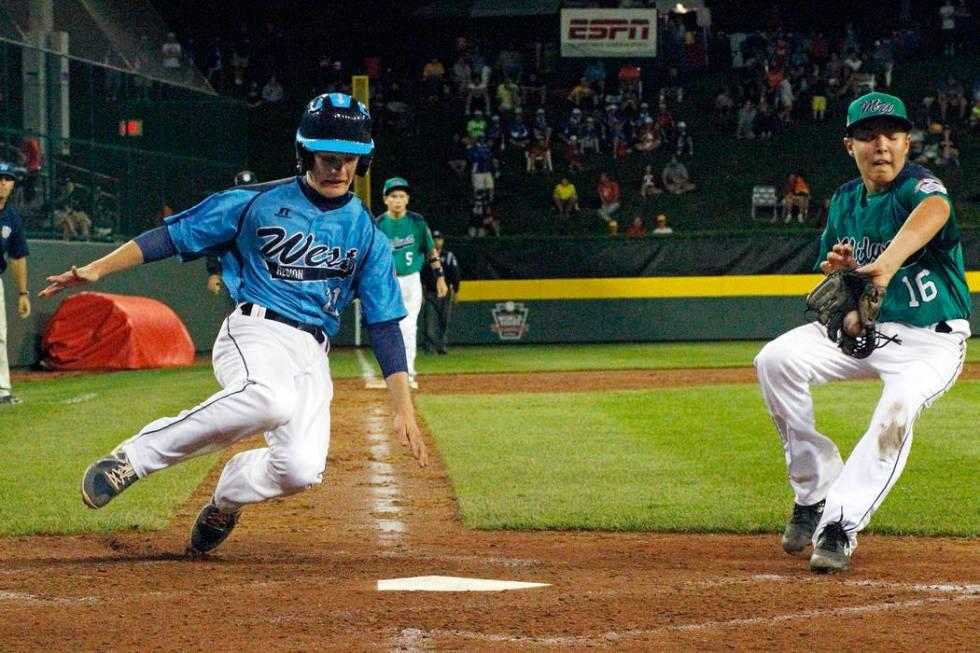 Las Vegas' Austin Kryszczuk, left, scores on a wild pitch by Rapid City, South Dakota pitcher D ...