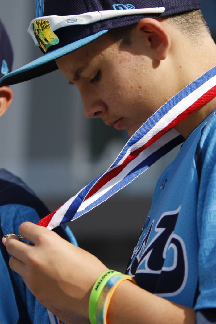 Mountain Ridge Little League player Andrew Matulich (14), right, looks at his medal as he stand ...