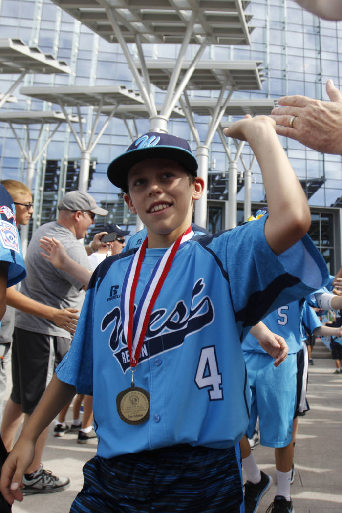 Mountain Ridge Little League player Drew Laspaluto (4), high fives fans as the team leaves for ...