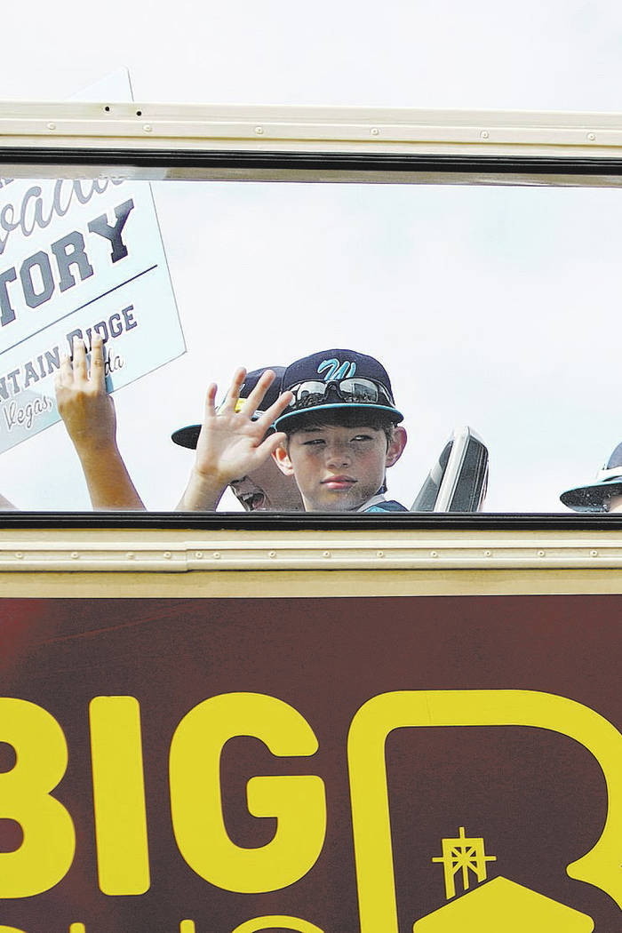 Mountain Ridge Little League players wave as they leave on a bus for their parade following a c ...
