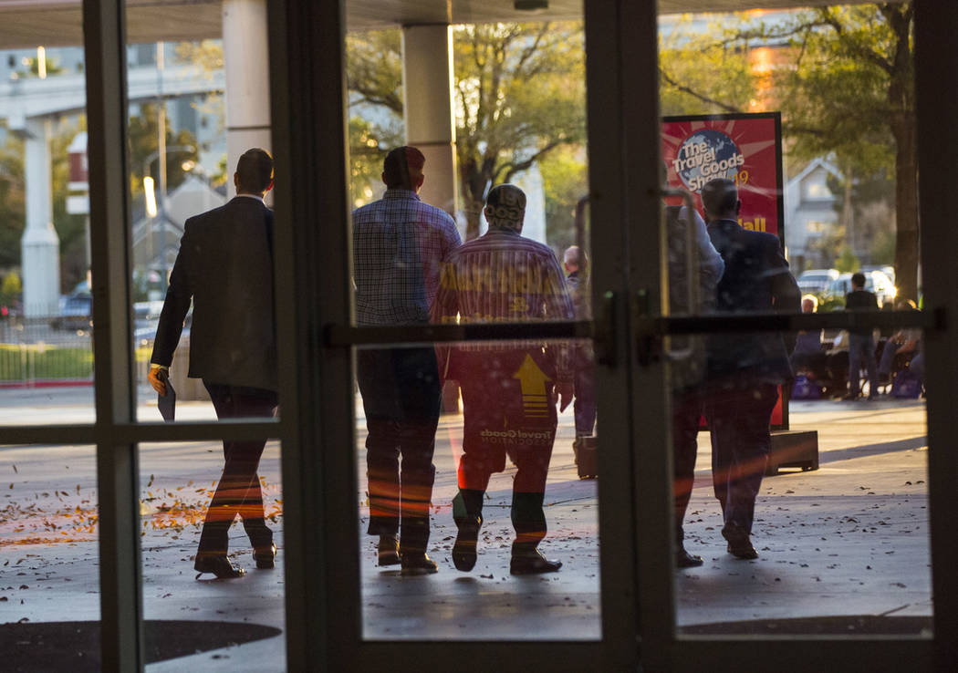 Plainclothes police officers walk out of the Las Vegas Convention Center after executing a sear ...