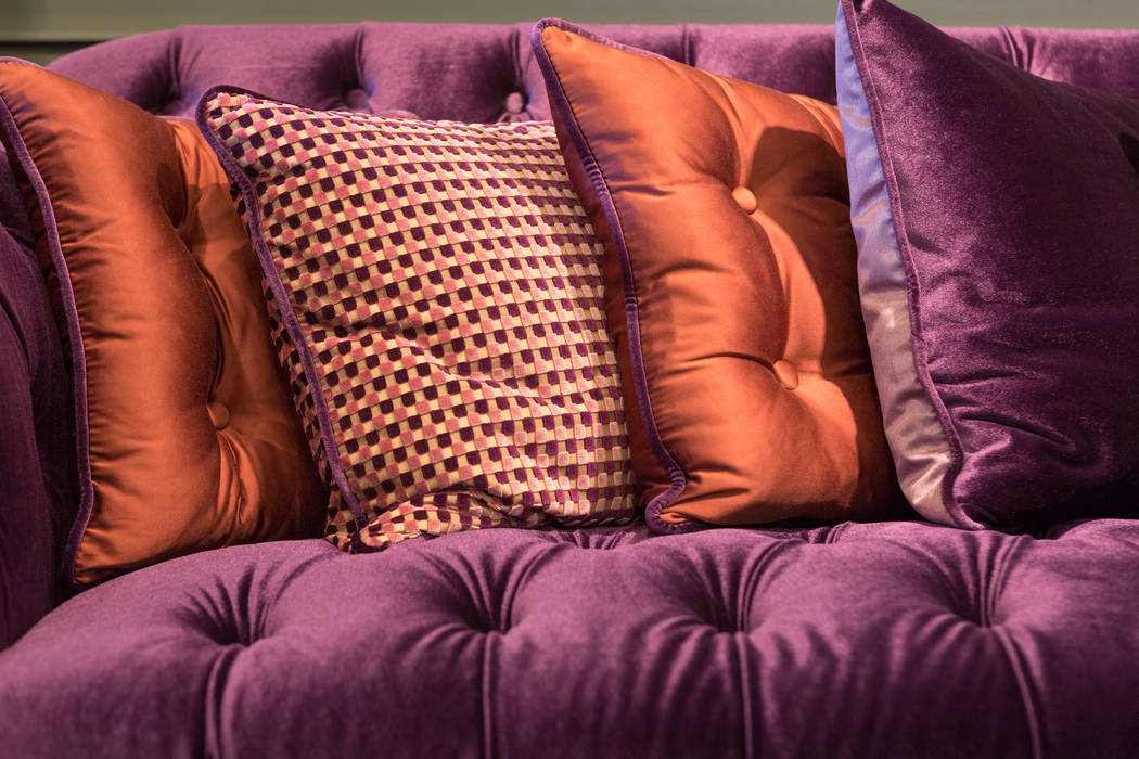 The sheen of satin pillows gives this violet velvet sofa a vintage style. (Getty Images)