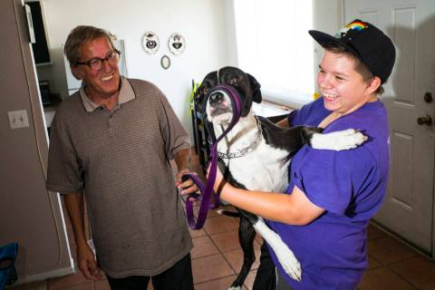 Fifteen-year-old Ryan Lauer, right, holds his dog, Cookie, as his father, Jack Lauer, looks on ...