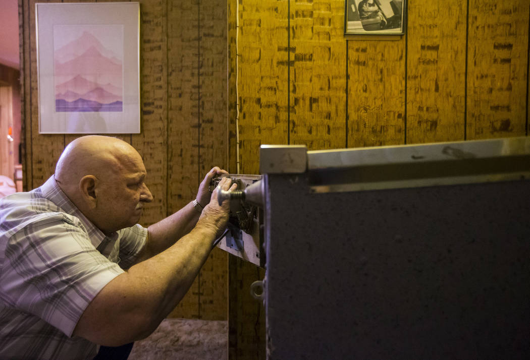 "Jerry Kaczmarek works on the ""Circus Queen"" bingo pinball machine at his home in Bull ..."