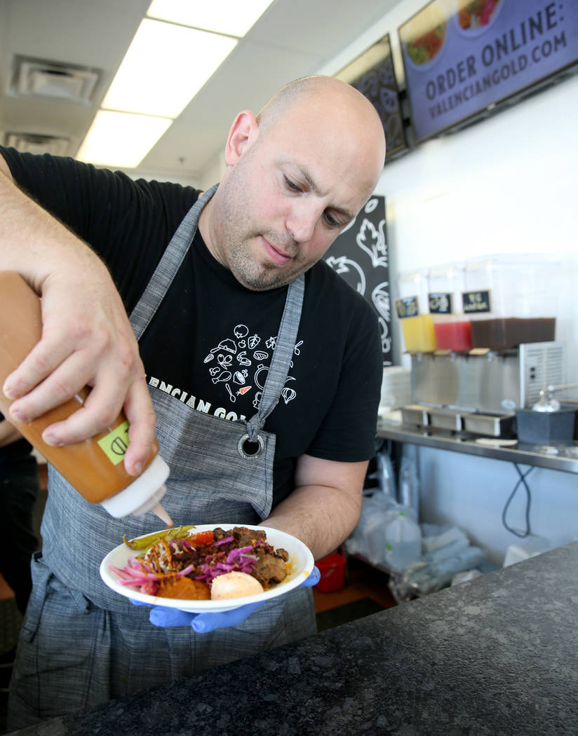 Chef and co-owner Jeffrey Weiss sauces a custom bowl at Valencian Gold in Las Vegas Thursday, J ...