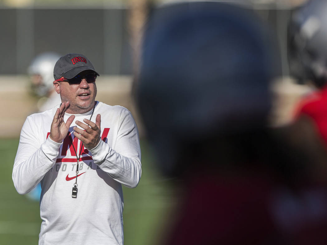 UNLV head football coach Tony Sanchez, left, fires up his team during the first day of training ...