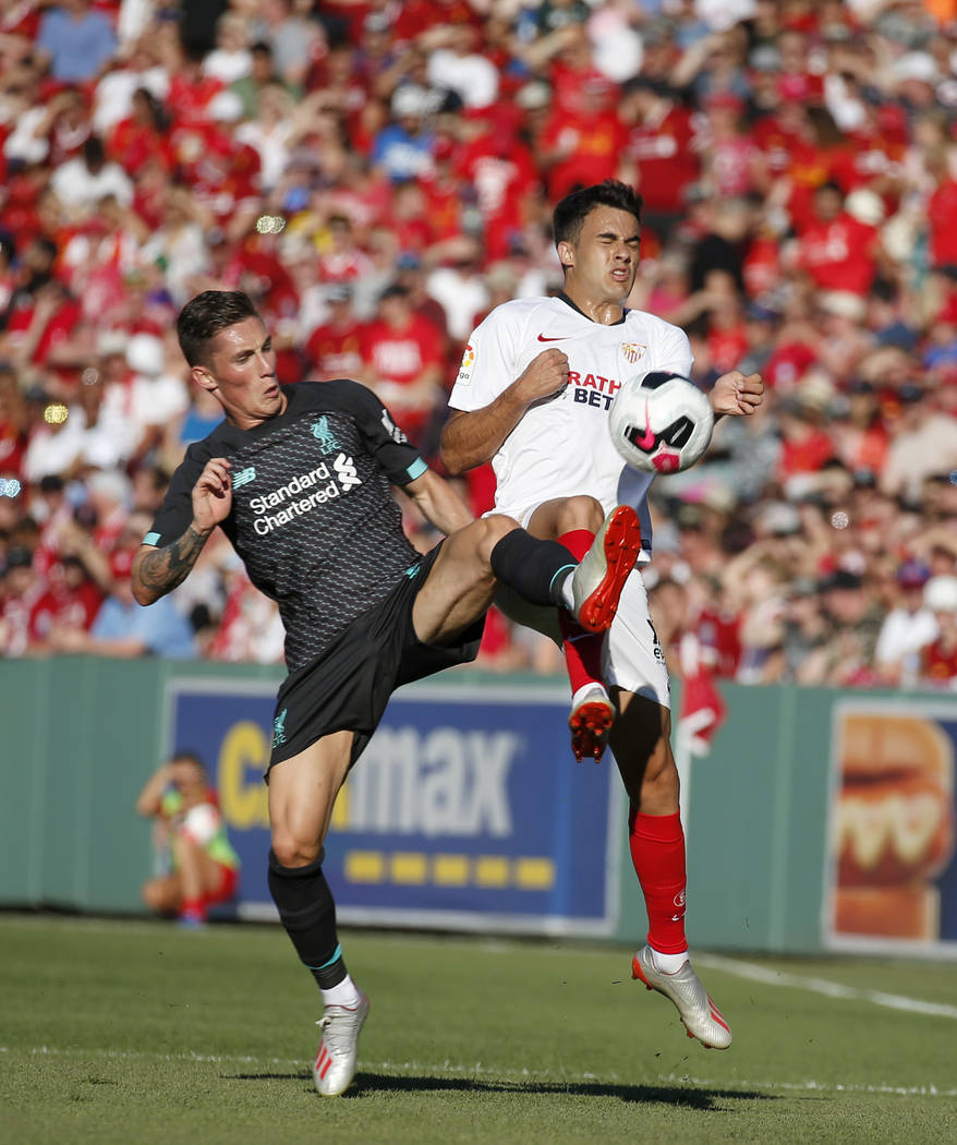 Liverpool's Harry Wilson, left, and Sevilla's Reguilon Rodriguez Sergio vie for the ball during ...