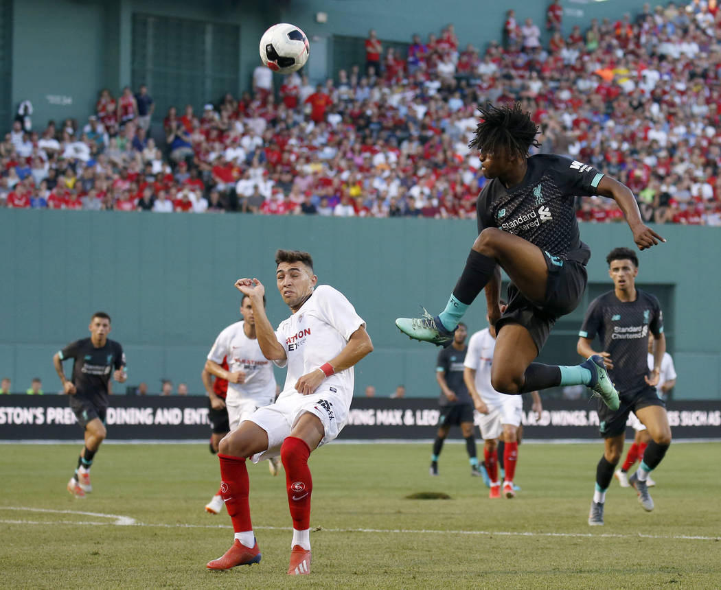 Liverpool's Yasser Larouci, front right, jumps for a ball against Sevilla's Munir during the se ...