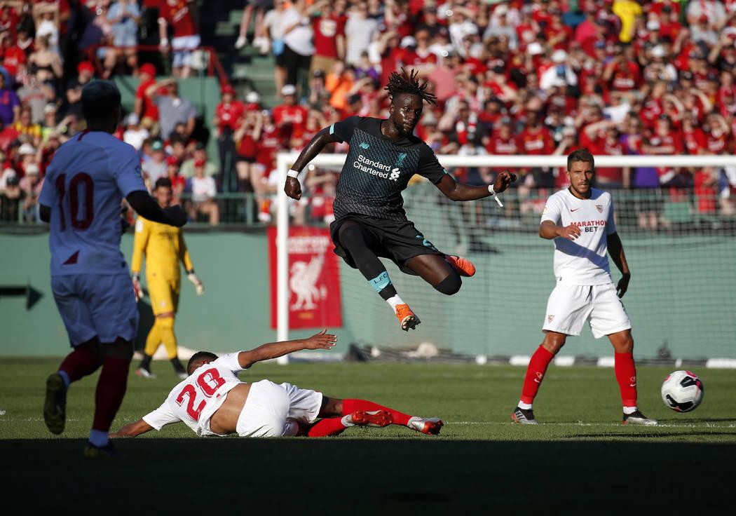 Liverpool's Divock Origi, center, leaps over Sevilla's Diego Carlos Santos Silva (20) during th ...