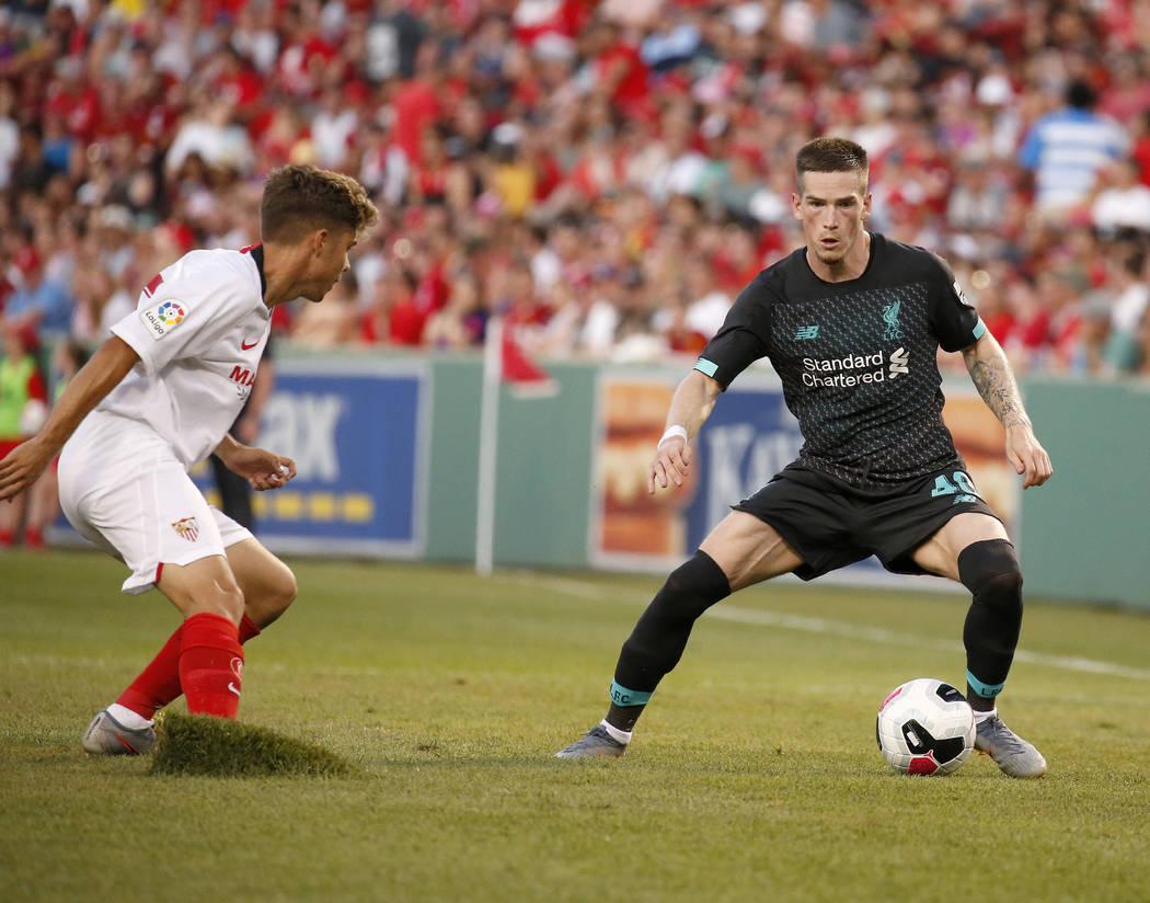 Sevilla's Alejandro Pozo, left, kicks up a piece of sod as he defends Liverpool's Ryan Kent (40 ...