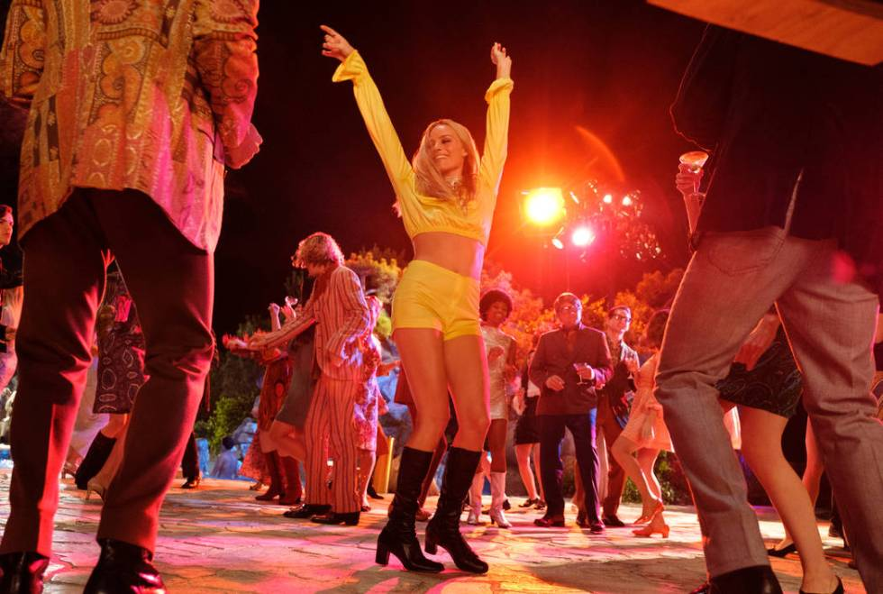 Sharon Tate (Margot Robbie) attends a party at the Playboy Mansion with Jay Sebring in a scene ...