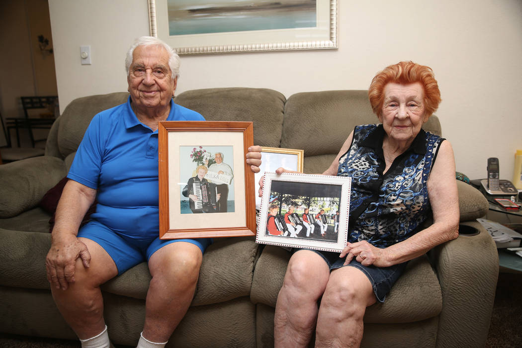 Joe Baykara, left, 93, and his wife Etta, 91, pose for a portrait with family photos at their h ...