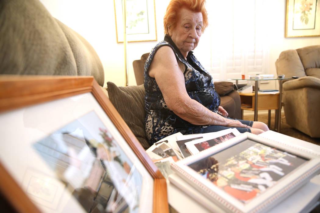 Etta Baykara, 91, shows family photos at her home in Las Vegas, Wednesday, Aug. 7, 2019. (Erik ...