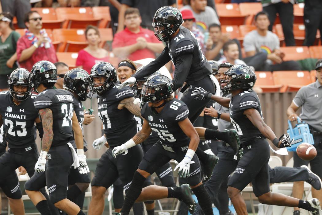 The Hawaii bench celebrates after Hawaii defensive back Kai Kaneshiro (24) intercepted an Arizo ...
