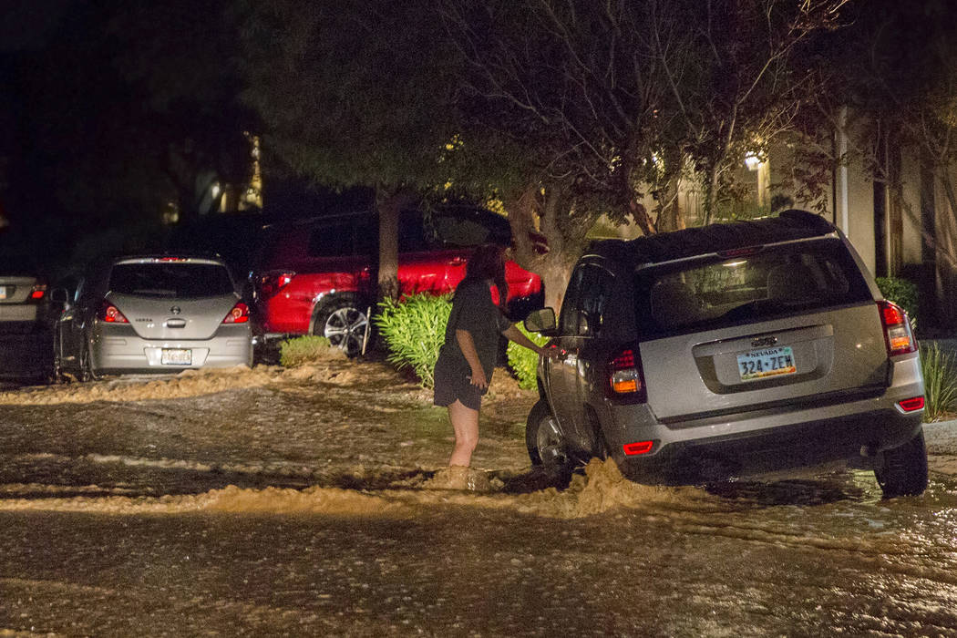 A southwest valley resident, right, tries to move her car out of flood waters on West Fitzwilli ...
