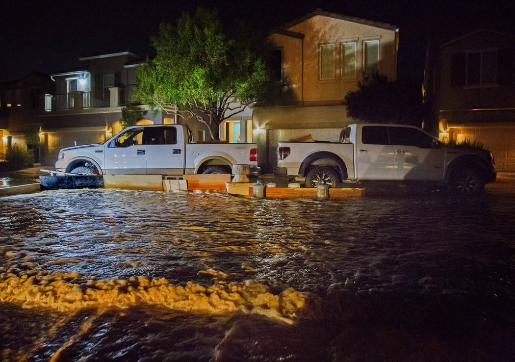 South west valley residents try to redirect flood waters with their trucks and wooden boards at ...