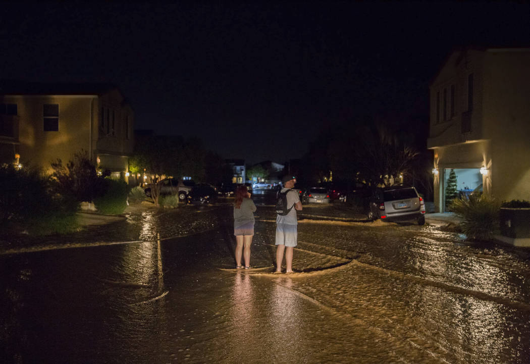 Southwest valley residents watch flood water flow past their homes near the intersection of Wes ...