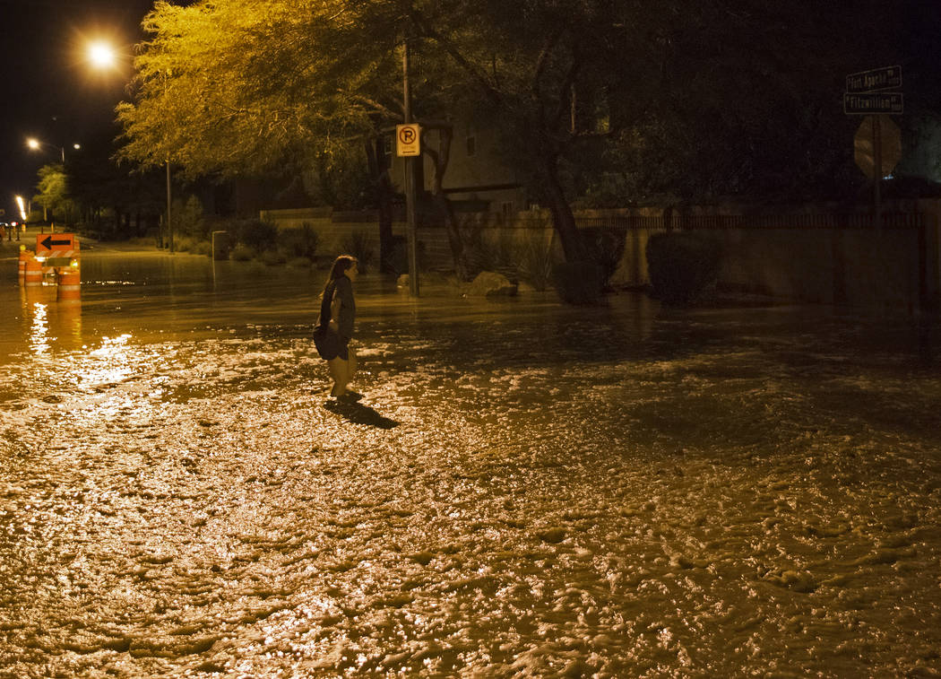 A southwest valley resident tries to cross flood waters nearing three feet deep at the intersec ...