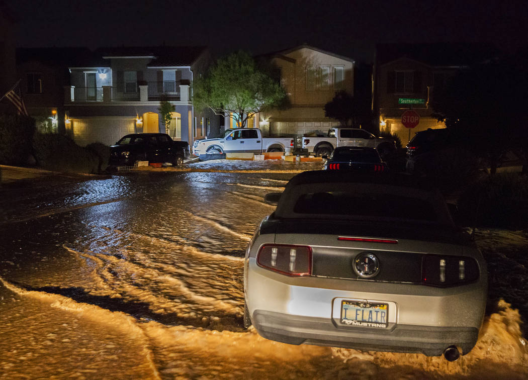 Flood water flows past vehicles and homes on West Fitzwilliam Avenue near South Fort Apache Roa ...
