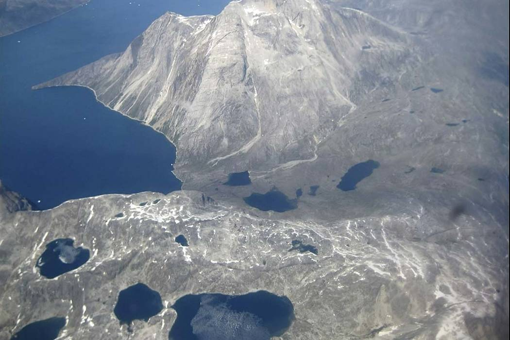 In this image taken on June 22, 2019, an aerial view of melt water lakes on the edge of an ice ...
