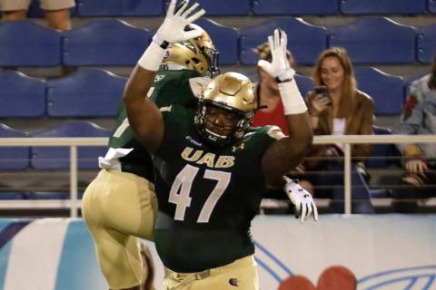 UAB defensive lineman Anthony Rush (47) celebrates with wide receiver Xavier Ubosi after Ubosi ...