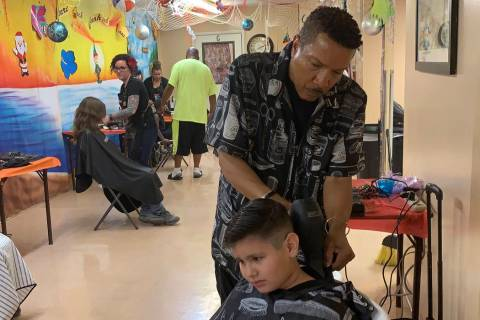 Thomas Rose, a volunteer at the Derfelt Back-to-School Haircuts & Eye Exams event, finishes a h ...
