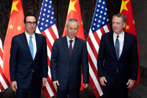 Chinese Vice Premier Liu He, center, poses with U.S. Trade Representative Robert Lighthizer, ri ...