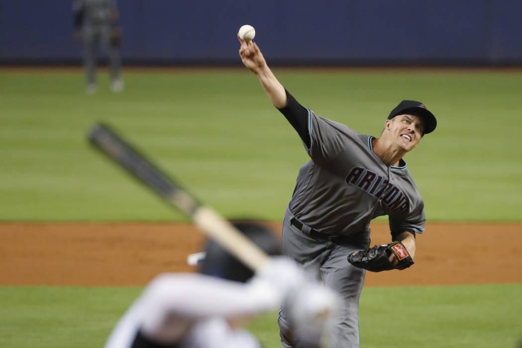 Arizona Diamondbacks' Zack Greinke, right, pitches to Garrett Cooper during the first inning of ...