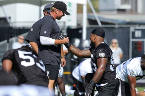 Oakland Raiders head coach Jon Gruden, left, shakes hands with linebacker Vontaze Burfict (55) ...