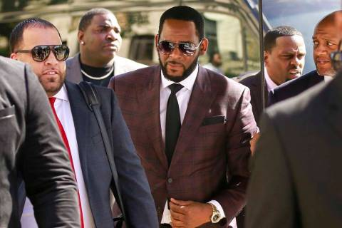 R&B singer R. Kelly, center, arrives at the Leighton Criminal Court building for an arraignment ...
