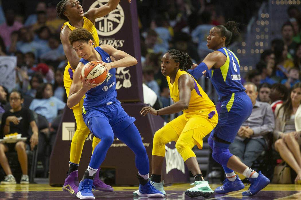 Dallas Wings' Isabelle Harrison, center, holds the ball during a WNBA basketball game against t ...