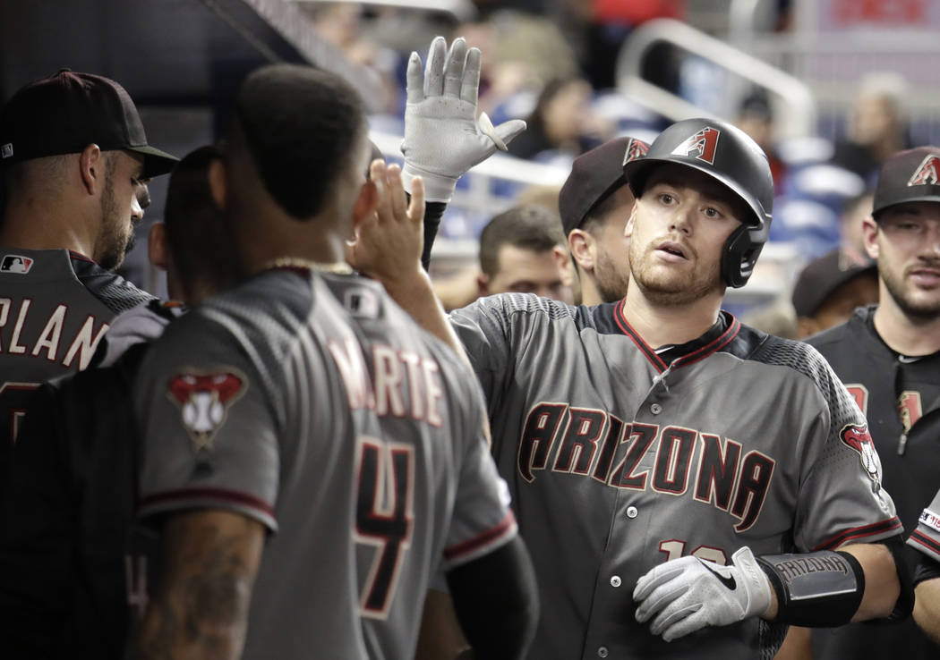 Arizona Diamondbacks' Nick Ahmed is congratulated after hitting a solo home run during the nint ...