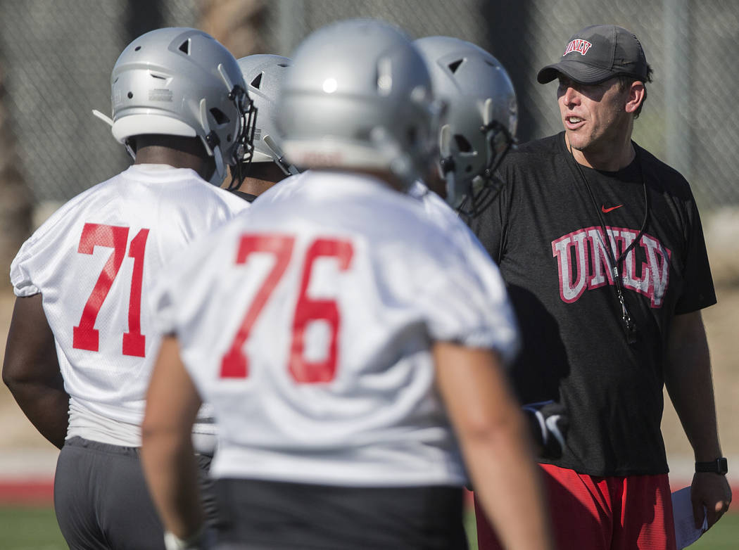 UNLV offensive coordinator Garin Justice, right, coaches up the Rebels during the first day of ...