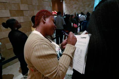 In this June 4, 2019 photo, job applicant Esta Williams, center, uses Tracy Simeton's back to f ...