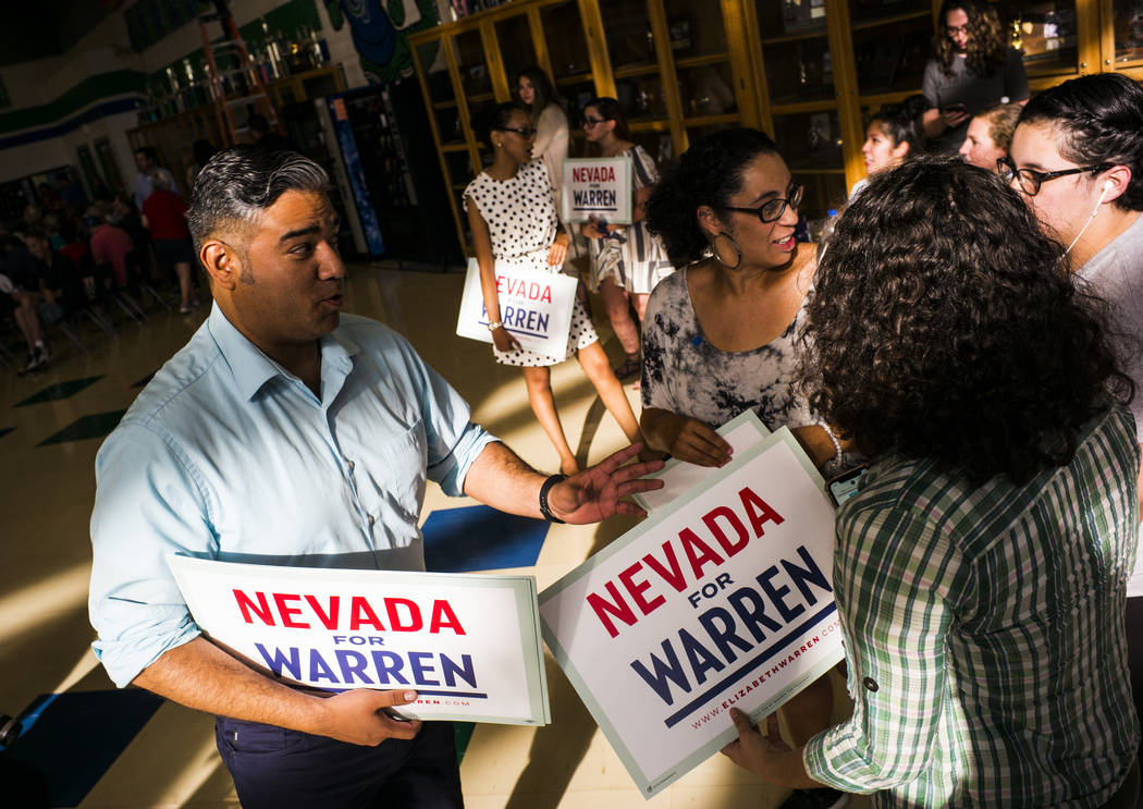 Organizer Richard Ponce, left, hands out signs in support of Democratic presidential candidate ...