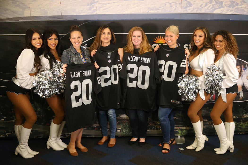 Allegiant employees pose with the Oakland Raiderettes during a celebration at the Allegiant hea ...