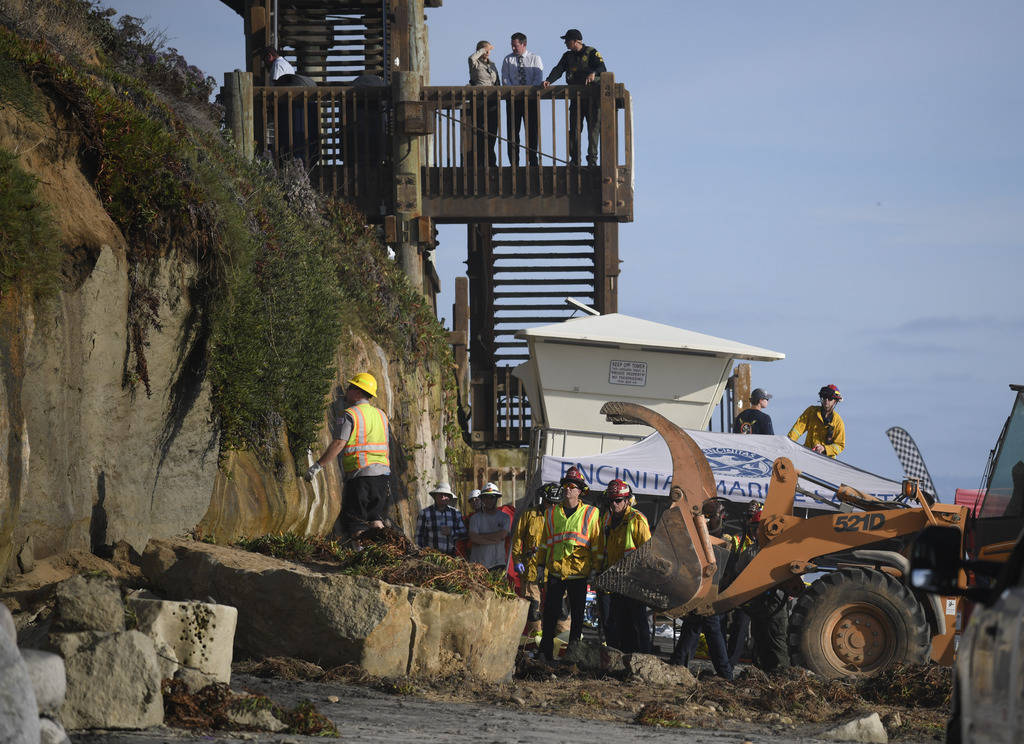 Search and rescue personnel work at the site of a cliff collapse at a popular beach Friday, Aug ...