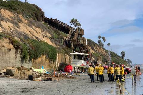 Lifeguards and search and rescue personnel work at the site of a cliff collapse at a popular be ...