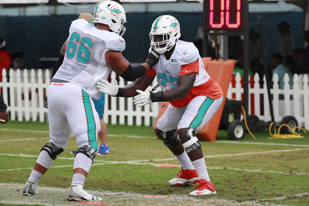 Miami Dolphins offensive tackles Aaron Monteiro (66) and Isaiah Prince (72) run drills at the t ...