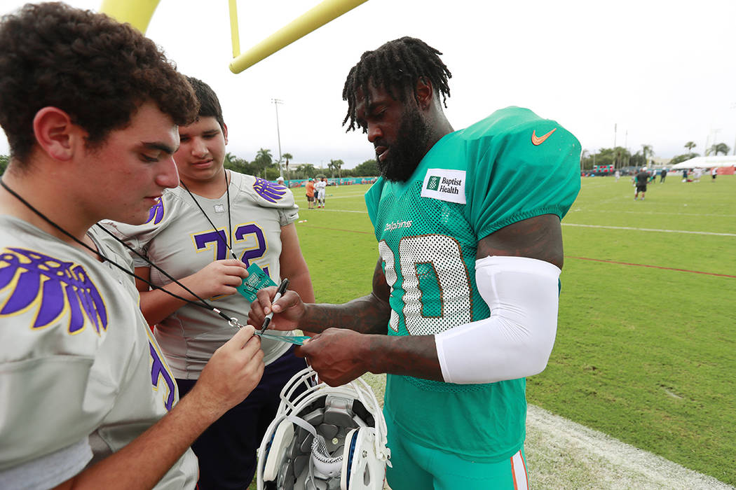 Miami Dolphins free safety Reshad Jones, right, signs autographs after the teams NFL football t ...