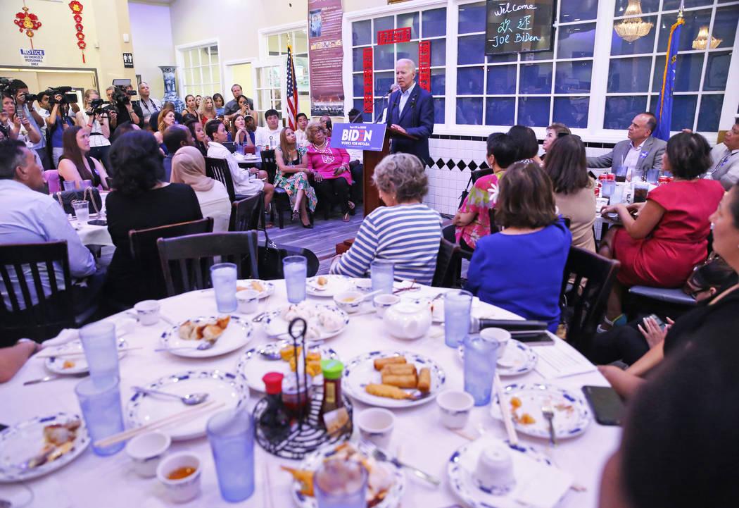 Attendees listen to Democratic presidential candidate former Vice President Joe Biden, top/midd ...