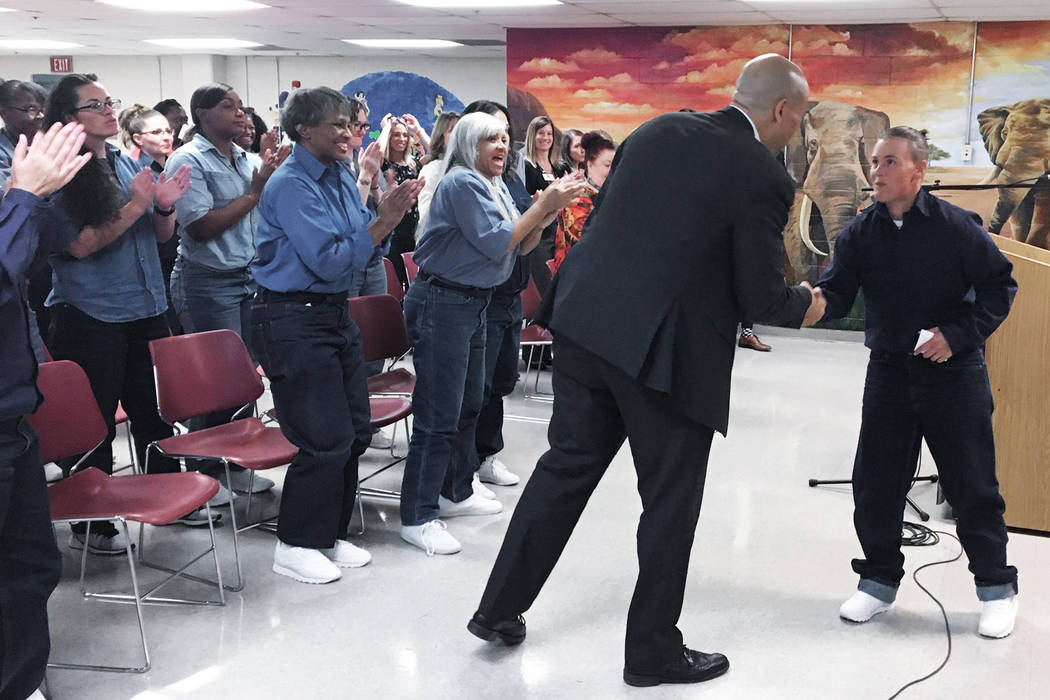 Democratic presidential candidate Sen. Cory Booker, D-N.J., shakes hands with an inmate on Satu ...