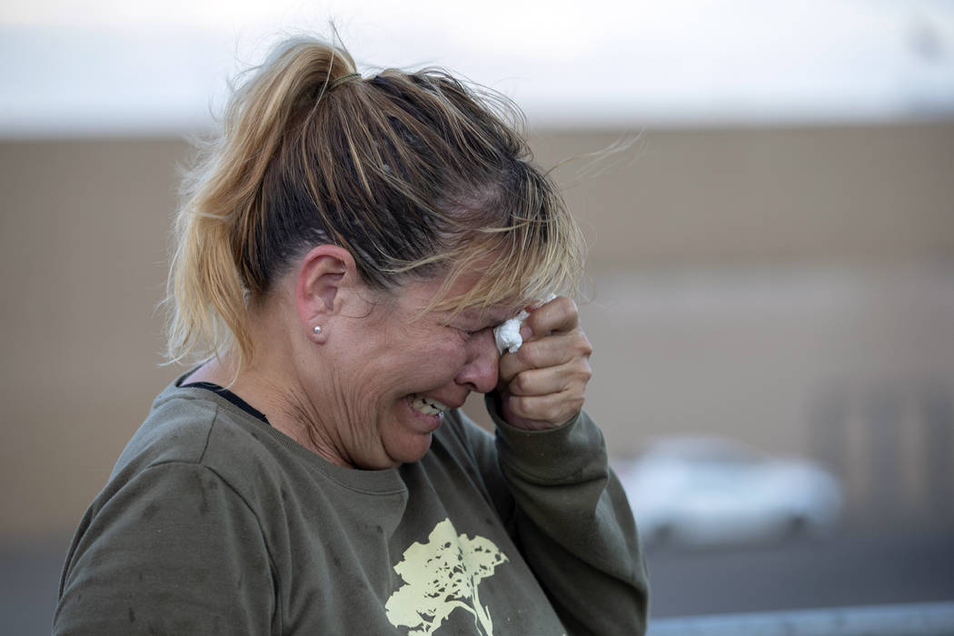 Edie Hallberg cries while speaking to police outside a Walmart store where a shooting occurred ...