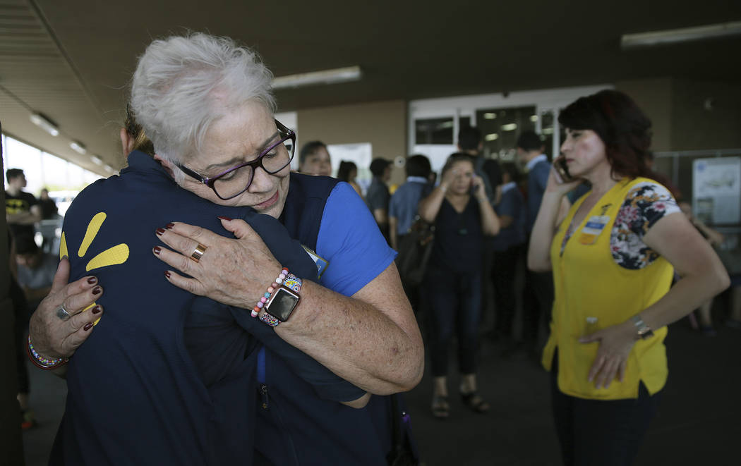 Walmart employees comfort one another after an active shooter opened fire at the store in El Pa ...