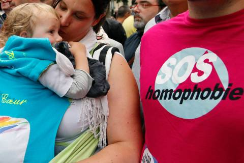 FILE - In this Saturday, June 28, 2014 file photo a woman kisses a baby next to a man wearing a ...