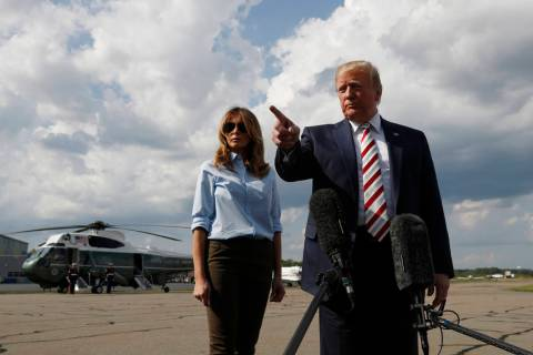 President Donald Trump, with first lady Melania Trump, speaks to the media before boarding Air ...