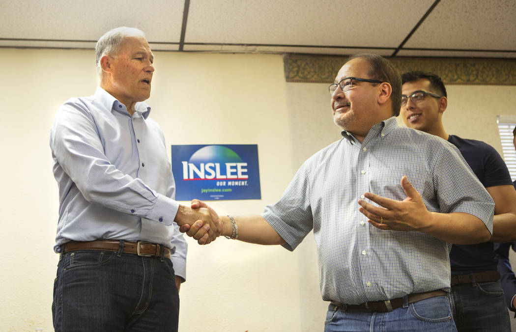 Democratic presidential candidate Washington Gov. Jay Inslee shakes the hand of the former Pres ...