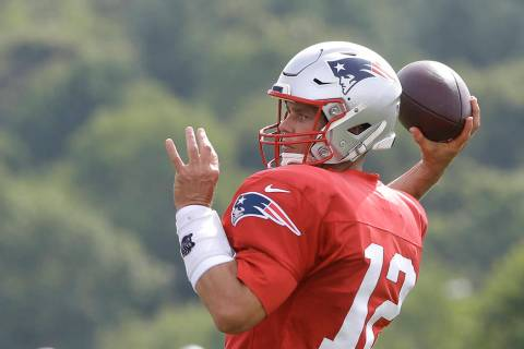 New England Patriots quarterback Tom Brady winds up to pass during an NFL football training cam ...