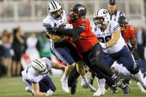 UNLV Rebels defensive lineman Nick Dehdashtian (98) tackles Brigham Young Cougars running back ...
