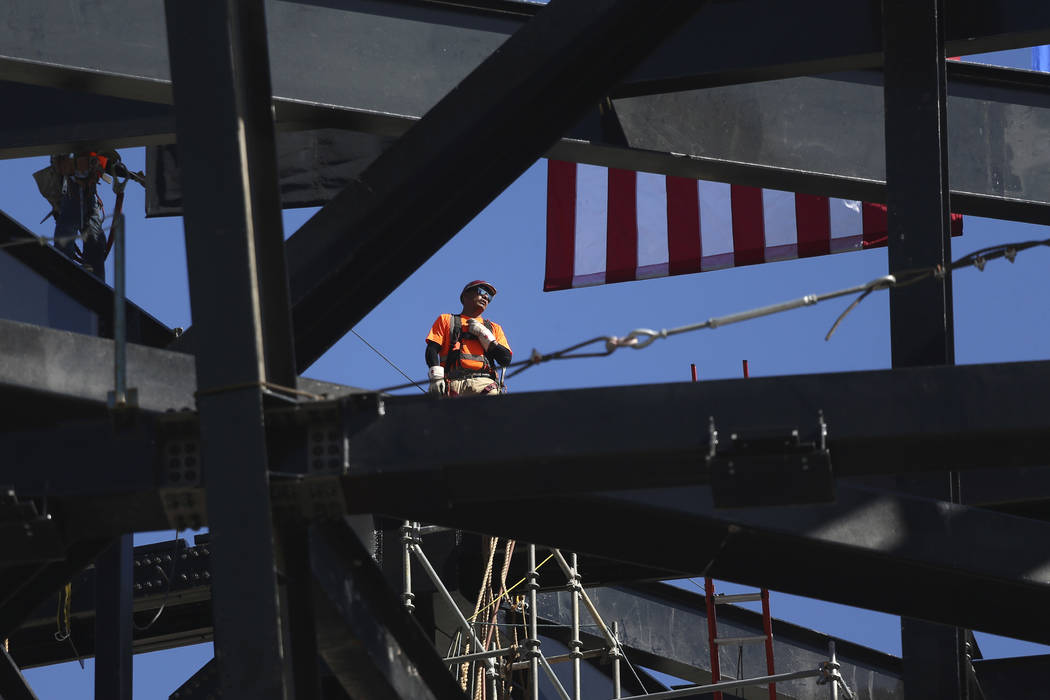 A worker helps install a steel beam during the Las Vegas Stadium Topping Out Ceremony in Las Ve ...